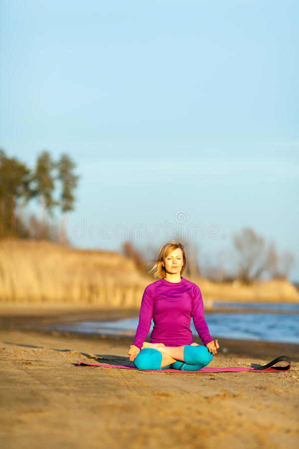 Young woman exercising yoga on sunset royalty free stock photos