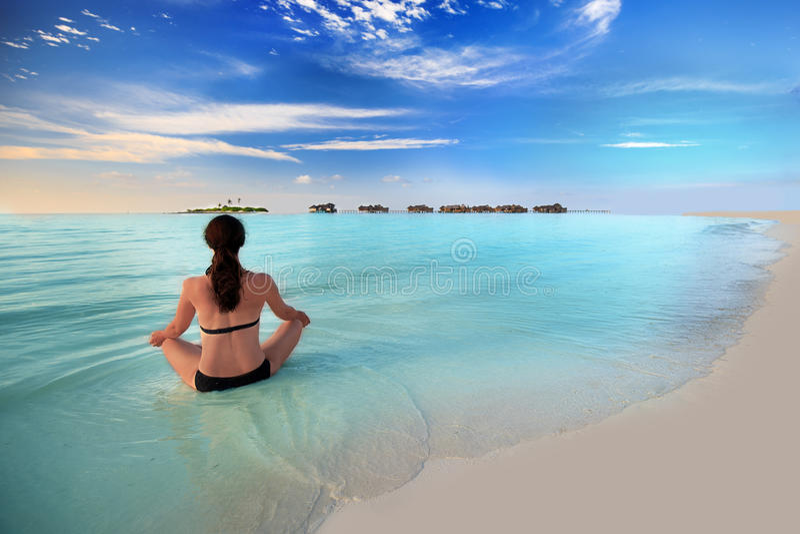 Young woman exercising yoga on tropical island stock image
