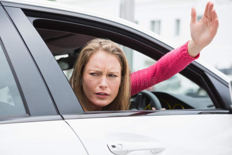 Young woman experiencing road rage. In her car stock photo