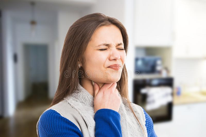 Young woman experiencing throat ache. Young woman experiencing strong throat ache because of flu cold as swallowing discomfort expression concept on indoor room stock photography