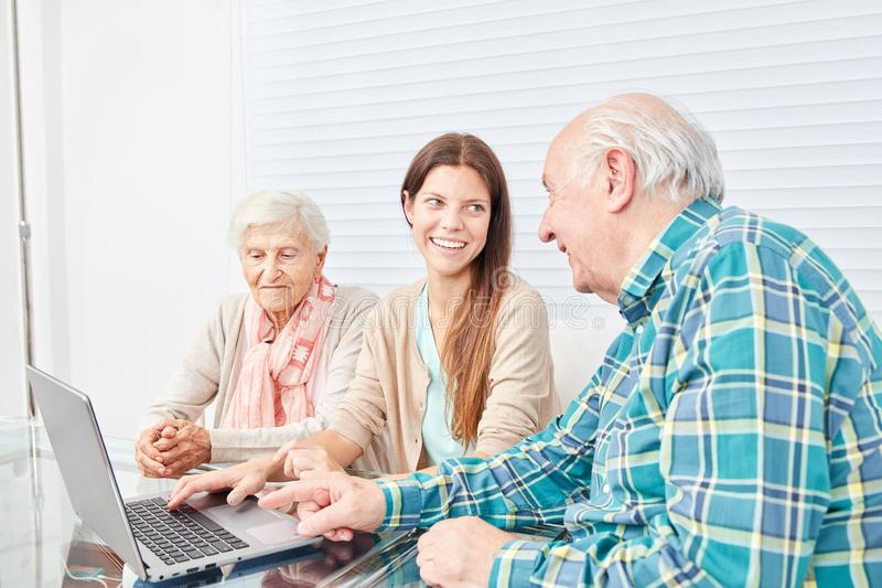 Young woman explains seniors couple the internet stock photos