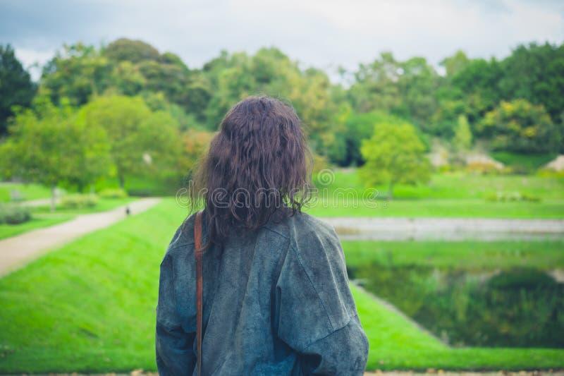 Young woman exploring formal garden. A young woman is exploring a formal garden with a large pond or lake stock photos
