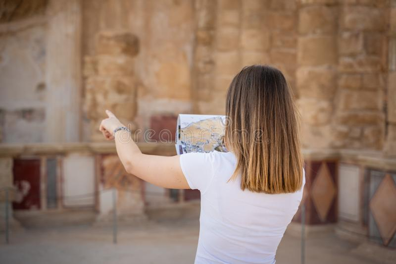 Young woman exploring the ruins of masada in israel. Tourist exploring the ruins of masada in Israel during a sunny day royalty free stock photography
