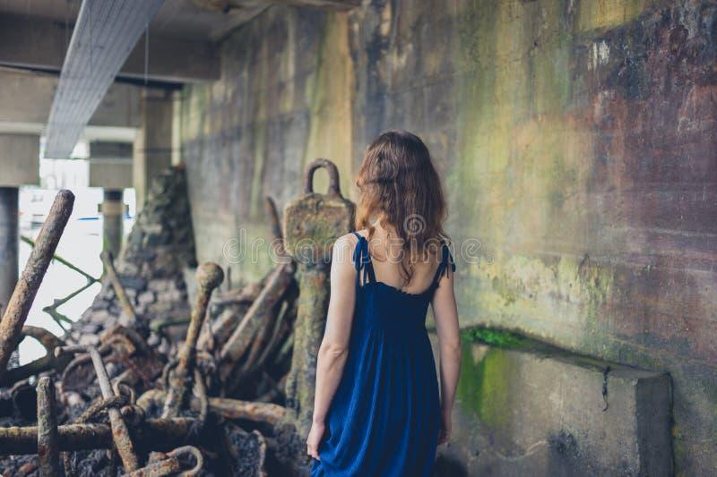 Young woman exploring shipyard. A young woman wearing a dress is exploring a shipyard with rusty old anchors royalty free stock photos