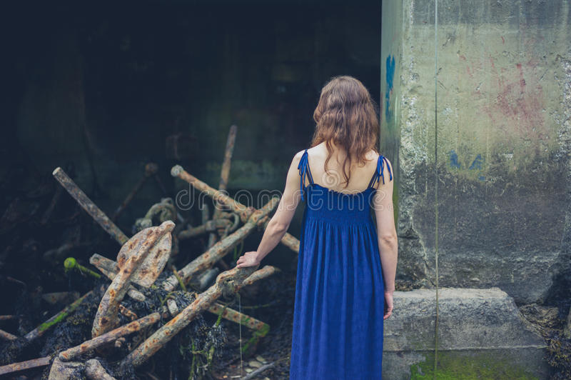 Young woman exploring shipyard. A young woman wearing a dress is exploring a shipyard with rusty old anchors royalty free stock images