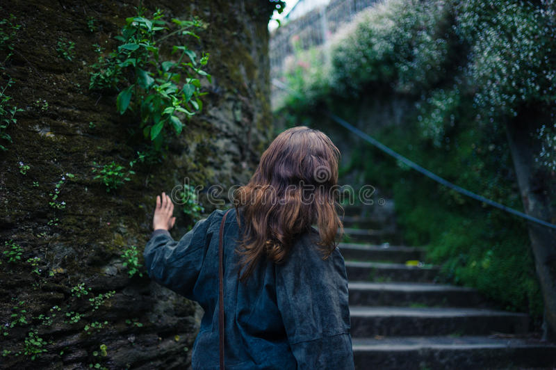 Young woman exploring stairs outside. A young woman is exploring some stairs in an alley outside royalty free stock photos