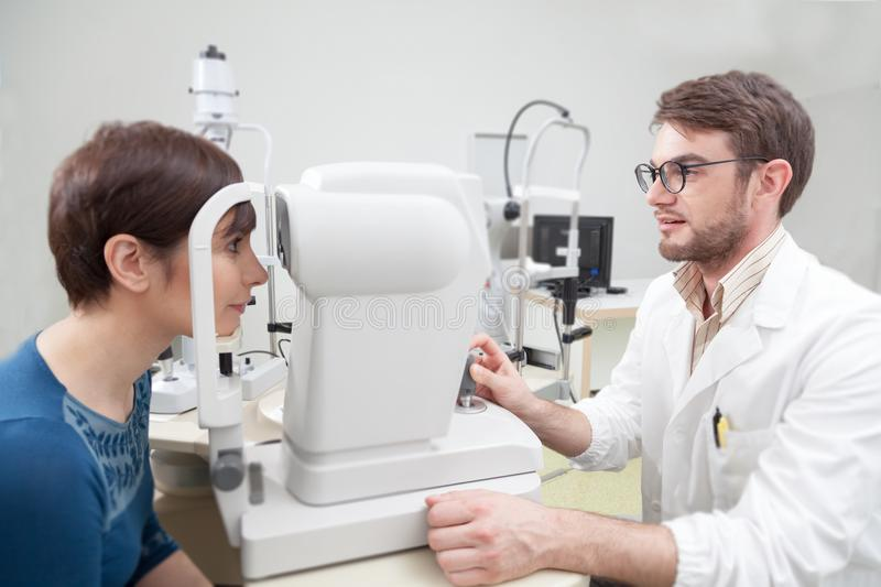 Young woman is during an eye exam with the ophthalmologist. Ophthalmologist in eyes clinic doing eye exam diagnostic with vision of patient by modern computer stock photo