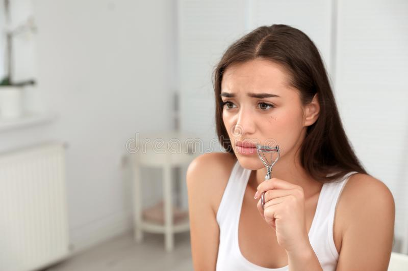 Young woman with eyelash loss problem holding curler, indoors. Young woman with eyelash loss problem holding curler indoors stock photography