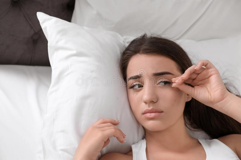 Young woman with eyelash loss problem resting. In bed royalty free stock images