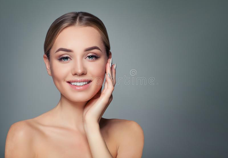 Young woman face. Healthy skin, cute smile. Perfect girl smiling. Facial treatment, skincare and cosmetology concept stock photos