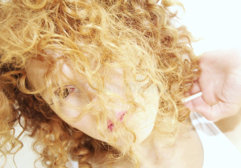Young woman with face hidden by curly hair stock photo