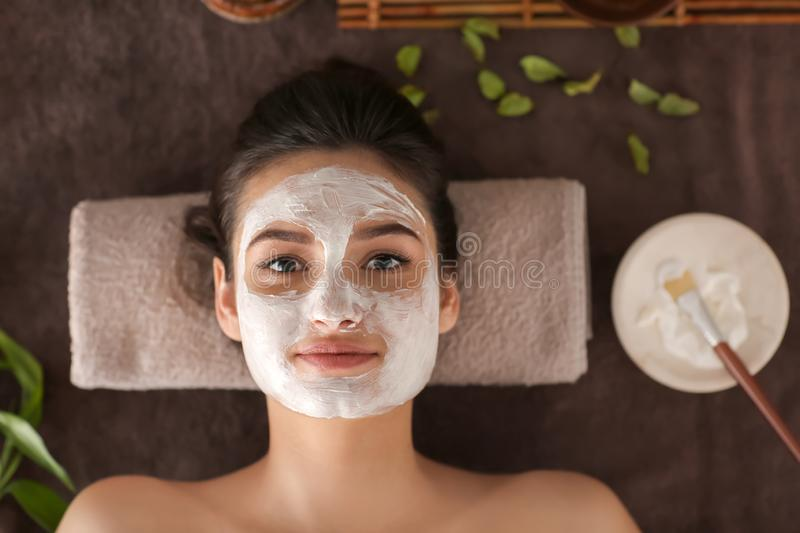 Young woman with face mask relaxing on massage table at spa salon, top view stock photos