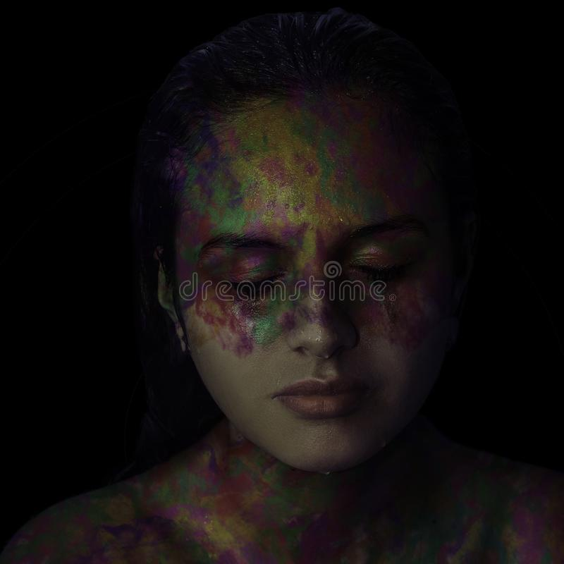 Young woman with face painted in metallic colors on black background stock photos