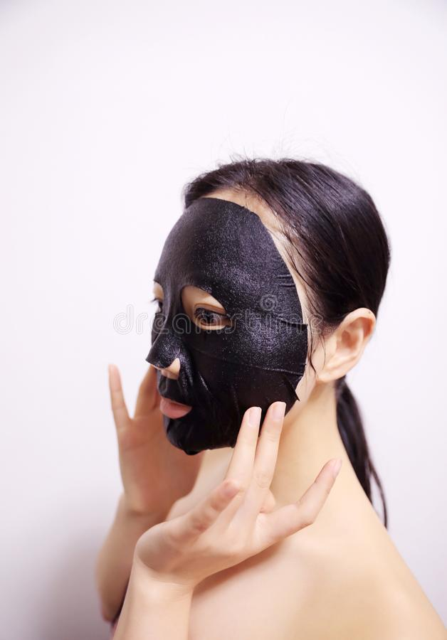 Facial black mask. Young woman with facial black mask on isolated white background stock images