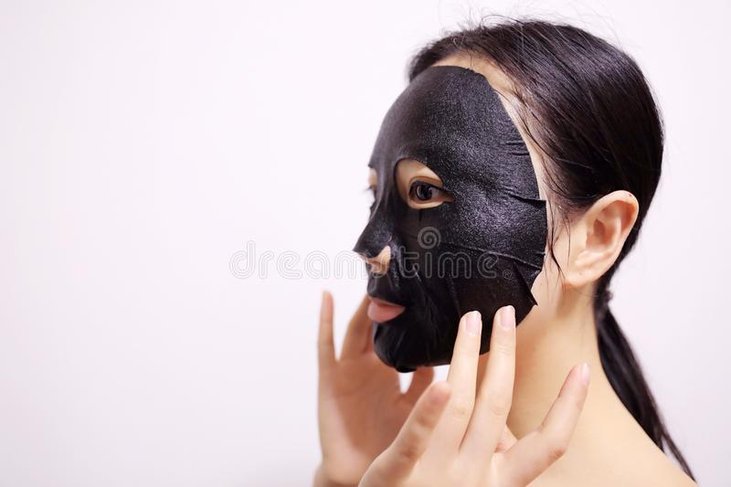 Facial black mask. Young woman with facial black mask on isolated white background royalty free stock image