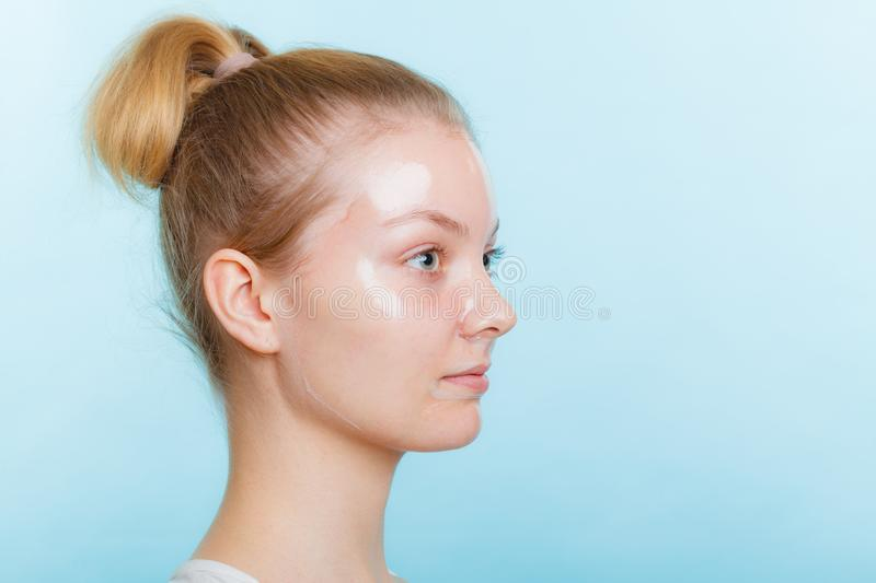 Woman in facial peel off mask. Young woman in facial peel off mask. Peeling. Beauty and skin care. Side view royalty free stock photos