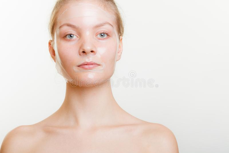 Woman in facial peel off mask. Young woman in facial peel off mask. Peeling. Beauty and skin care. Studio shot on gray royalty free stock photos