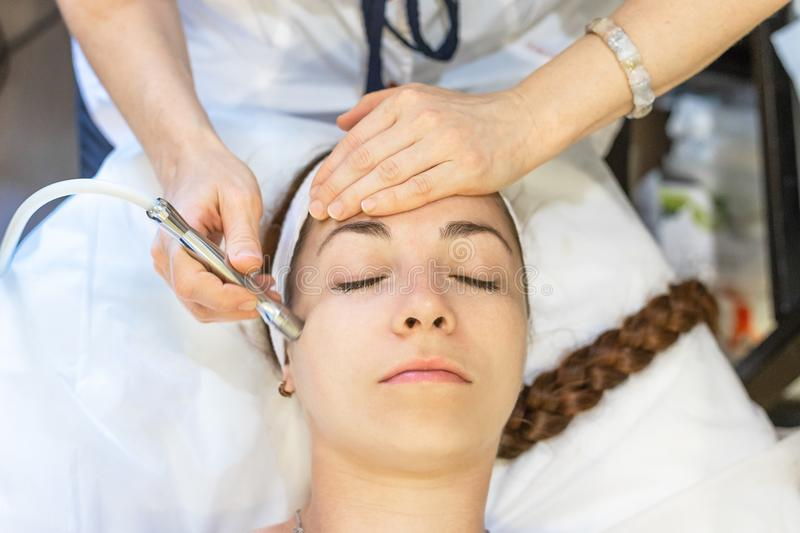 Young woman at facial skin cleaning procedure. Cosmetologist working with face using special medical equipment. Patient lies with close eyes, top view. Beauty royalty free stock image
