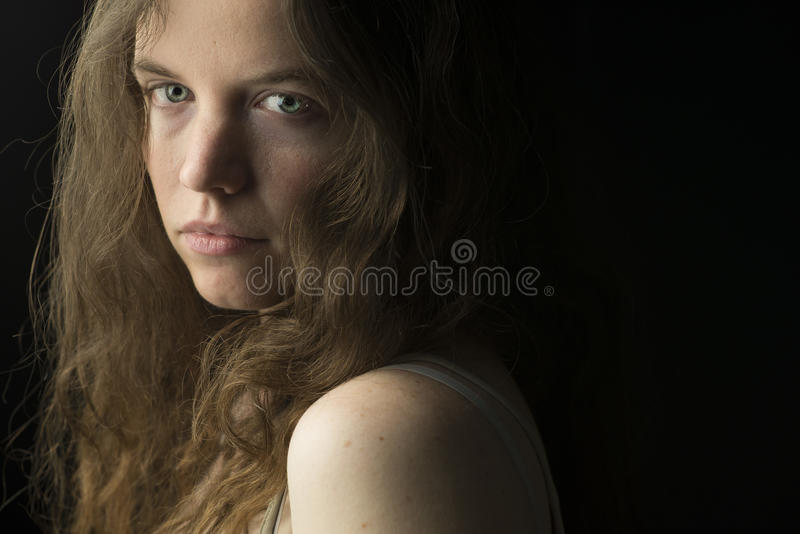 Young Woman with Fair Skin, Blue Eyes and Light Brown Curly Hair in Dramatic Lighting stock photo