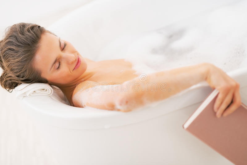 Young woman fall asleep while reading book in bathtub stock images