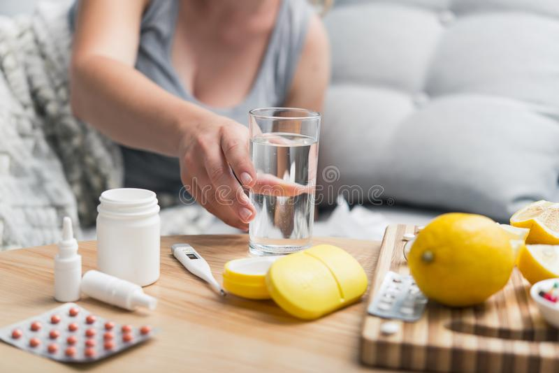 Young woman fall ill cold and flu was treated at home on the couch. Takes medication and drinks with a glass of water royalty free stock image