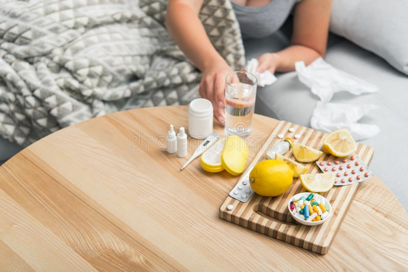 Young woman fall ill cold and flu was treated at home on the couch. Takes medication and drinks with a glass of water royalty free stock photography