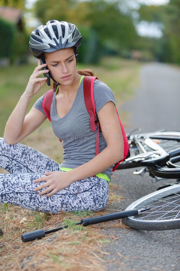 Young woman fallen down from bicycle calling for help royalty free stock photo