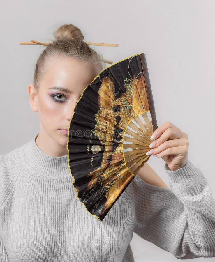 Young woman with a fan. Portrait of a young woman with a fan stock images