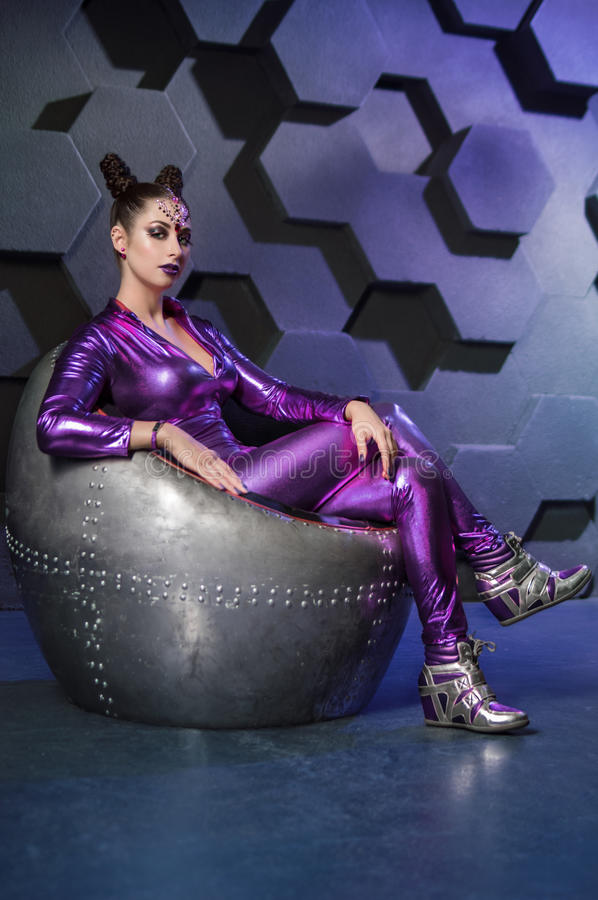 Young woman fantasy violet costume. On techno background stock image