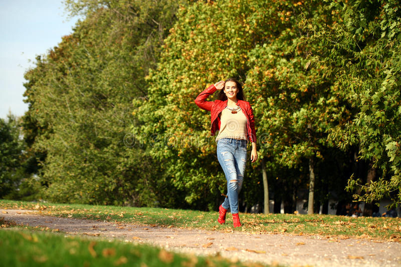 Young woman in fashion red jacket and blue jeans walking in autu. Young beautiful woman in fashion red jacket and blue jeans walking in autumn park stock images