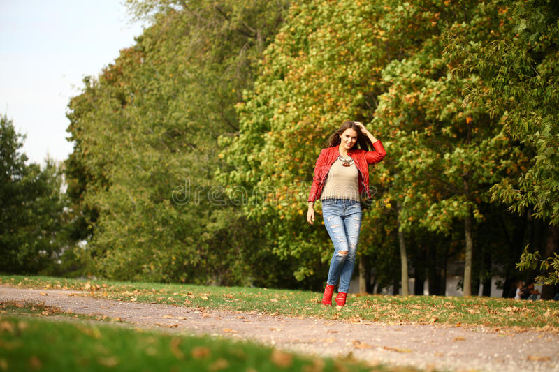 Young woman in fashion red jacket and blue jeans walking in autu. Young beautiful woman in fashion red jacket and blue jeans walking in autumn park stock photos