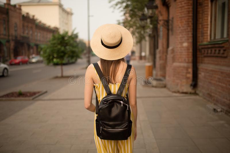 Young woman in fashionable yellow clothes is walking around the city. The road, a pedestrian royalty free stock image