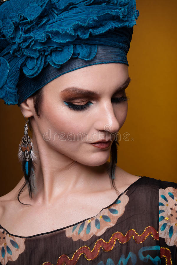 Young woman fasion makeup blue brown. On the yellow-gold background stock photos