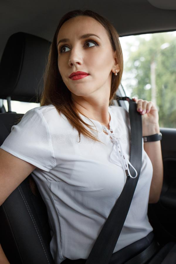 Young woman fastening seat belt in the car. stock image