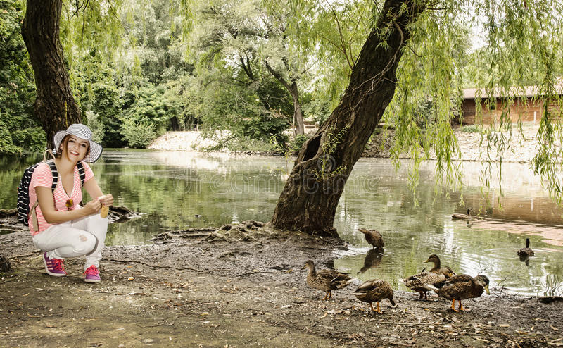 Young woman is feeding the group of duck in the city park royalty free stock image