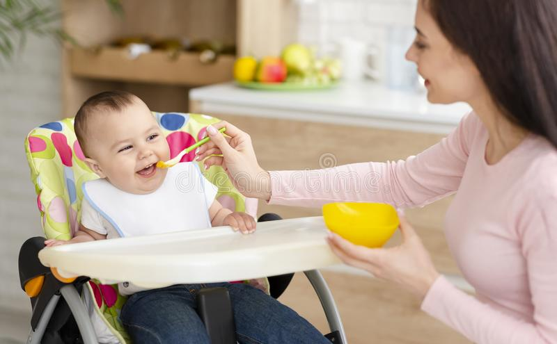 Young woman feeding her cute toddler in kitchen stock image