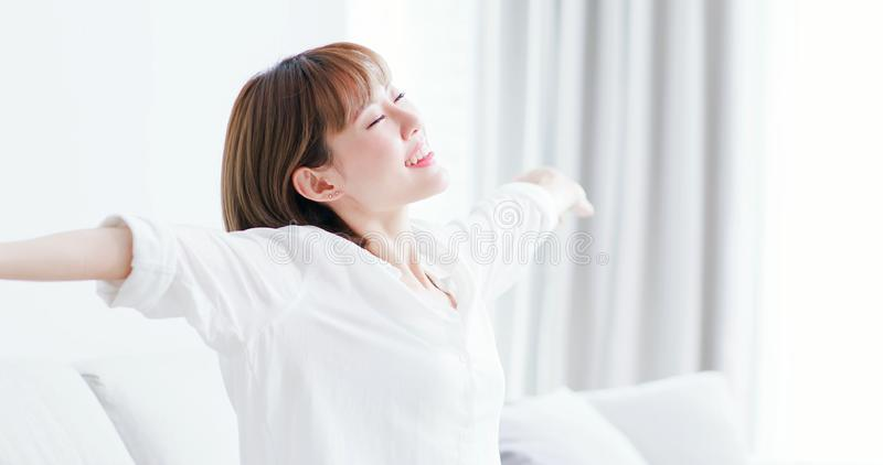 Woman feel carefree at home. Young woman feel carefree and stretch arm to take a deep breath at home royalty free stock photography