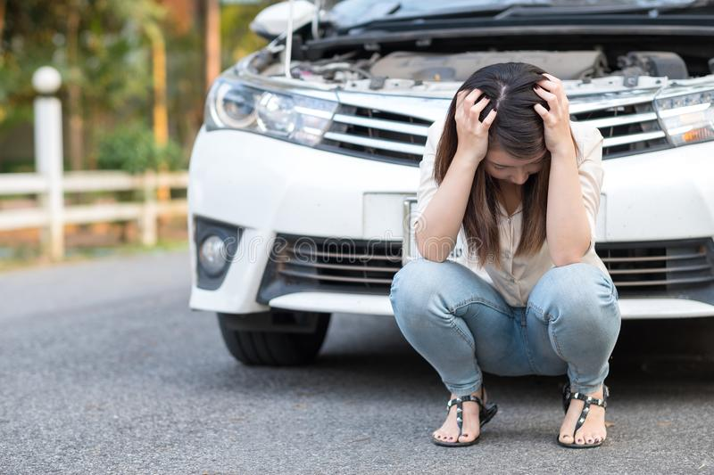 Young asian woman feel sad sitting near the broken down car royalty free stock photography