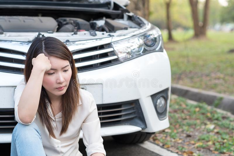 Young woman sitting near the broken down car stock photos