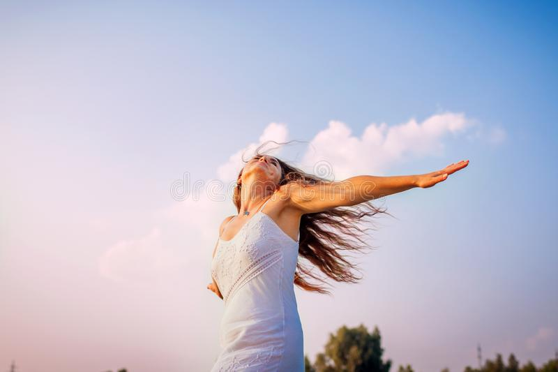 Young woman feeling free and happy raising arms and spinning around outdoors at sunset stock photography