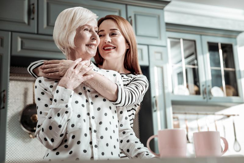 Young woman feeling happy while meeting her mother and hugging her royalty free stock photos