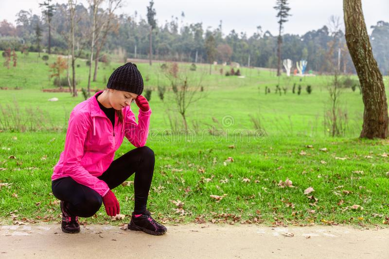 Young woman feeling lightheaded or with headache after train on a cold winter day on the training track of an urban park. stock photo