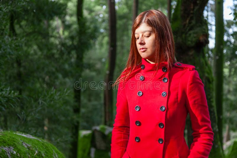 Young woman feeling sad walking alone on forest path wearing red long coat stock photo