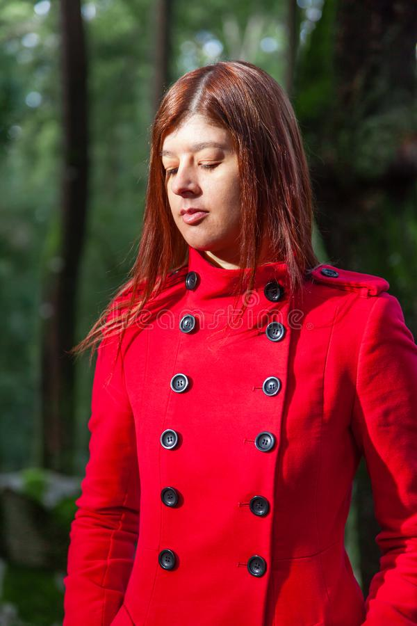 Young woman feeling sad walking alone on forest path wearing red long coat stock image