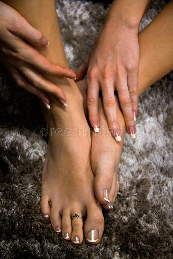 Young woman feet and hands close up above view, girl touching her feet on black and white artistic abstract background, long nails. Natural beauty woman feet royalty free stock image