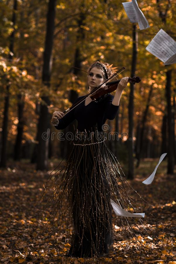 Attractive giril fiddle violin over the flying music paper and fall park background royalty free stock photos