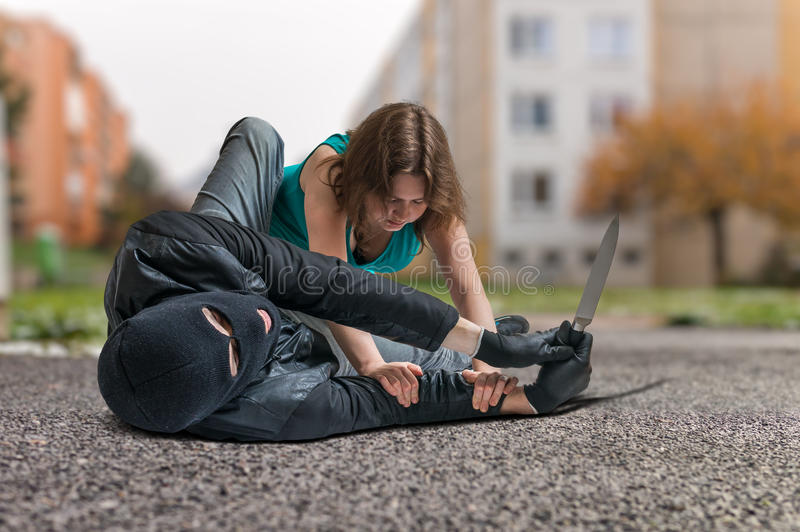 Young woman is fighting with armed thief with knife. Self defense concept royalty free stock photos