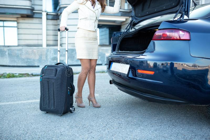 Young woman figuring how to place her luggage. Inside the car stock photography