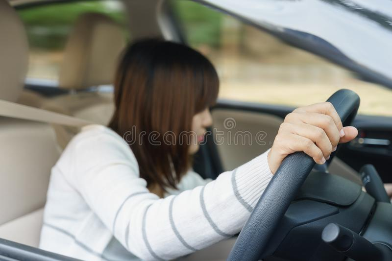 Young woman find something in drawer front of car with carelessness while driving - accident concept. Young woman find something in drawer front of car with stock photo