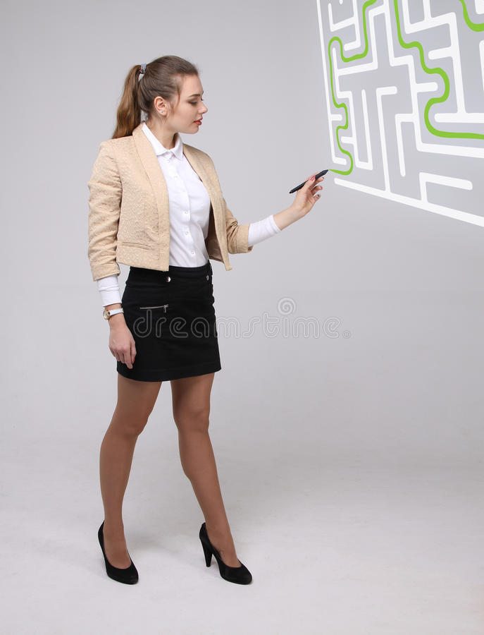 Young woman finding the maze solution, writing on whiteboard. stock photos